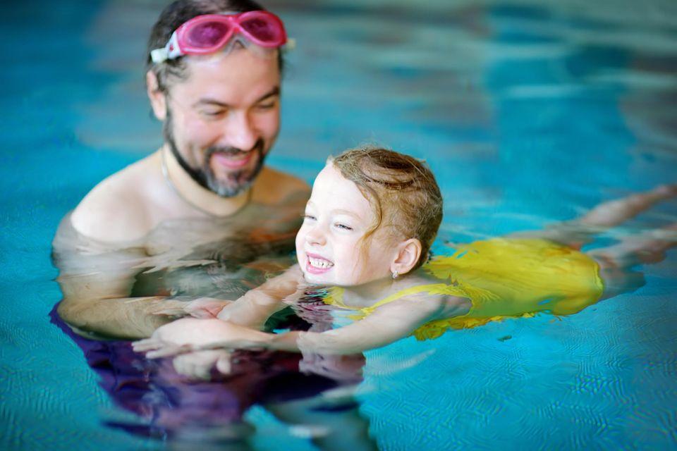 Schwimmen üben: Mädchen lernt schwimmen