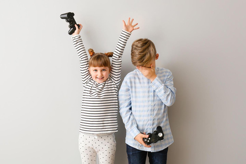 Verlieren lernen: Kinder, die eine Videospielkonsole in der Hand halten