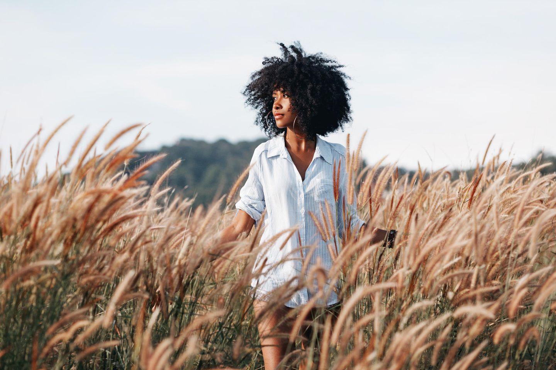 """7 Warnsignale, die viele für """"normal"""" halten: Junge Schwarze Frau schaut nachdenklich auf ein Feld hinaus."""