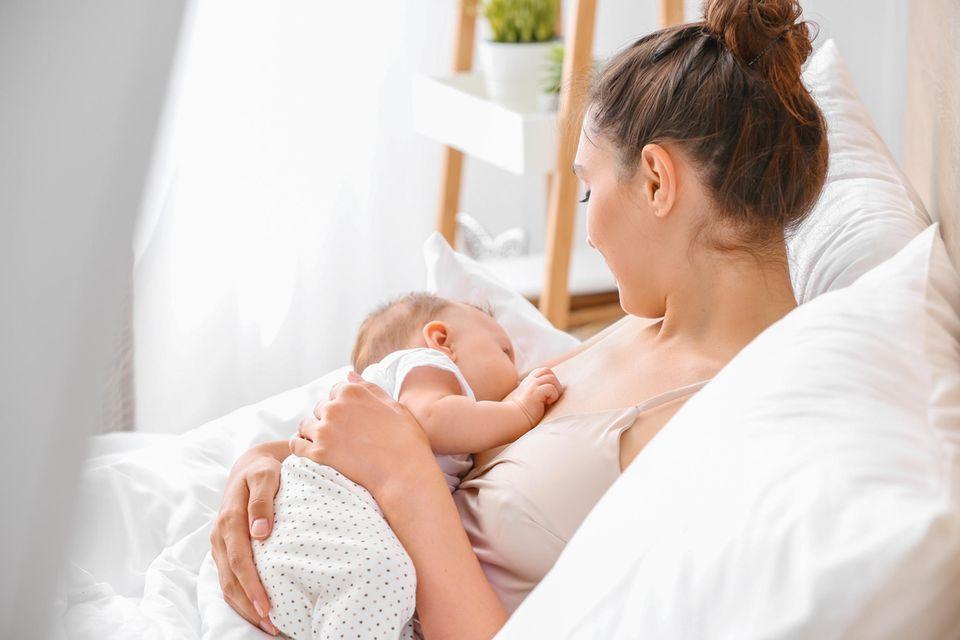 Eine junge Mutter stillt ihr Baby im Bett.