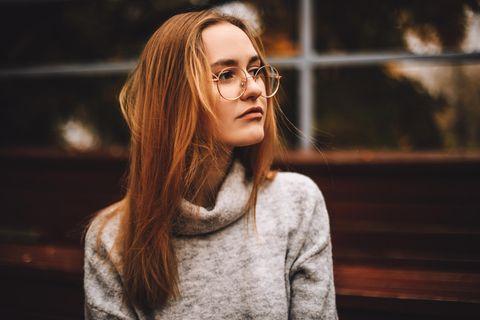 Diese 5 Gedanken helfen dir gegen das Gefühl, nicht gut genug zu sein: Frau mit langen Haaren und Brille schaut ernst.
