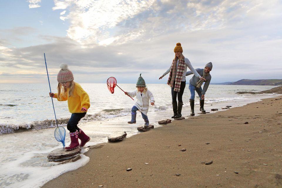Umweltfreundlich: Familie am Strand mit Kescher in der Hand