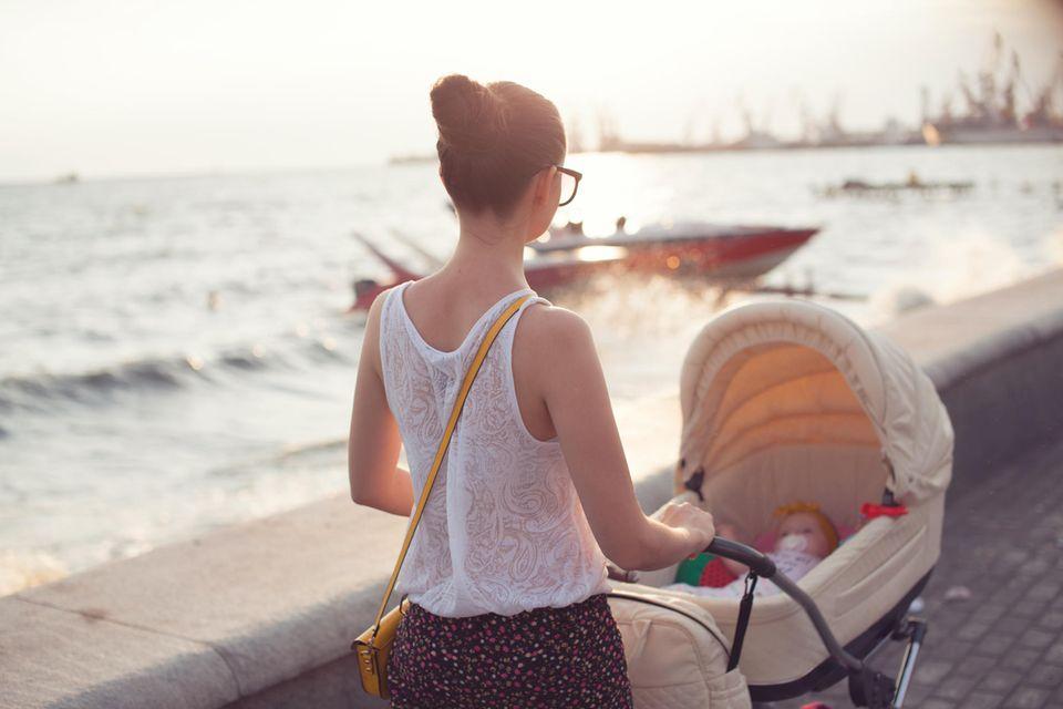 Eine Mutter spaziert mit ihrem Baby entlang der Promenade.