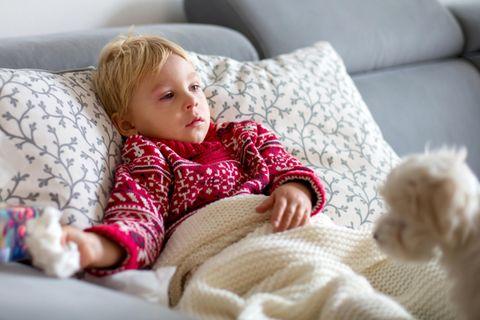 Kranker kleiner Junge liegt gut zugedeckt auf dem Sofa