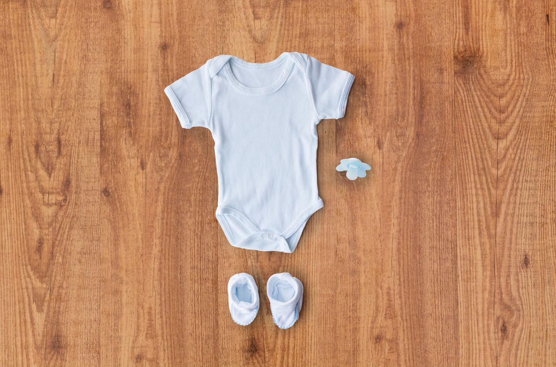Nachhaltige Kleidung: Babyoutfit liegt auf einem Holztisch