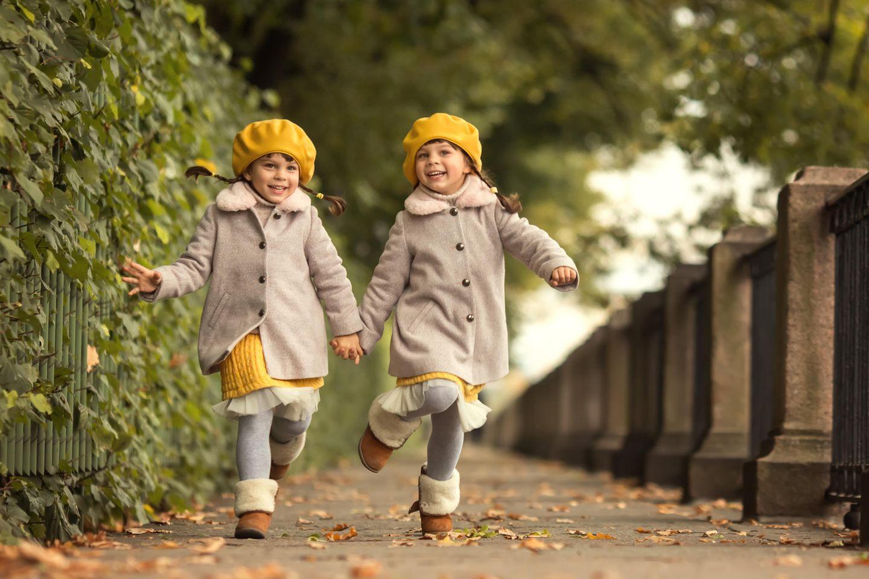 Zwillingsklischees: Lachende Mädchen halten sich an den Händen