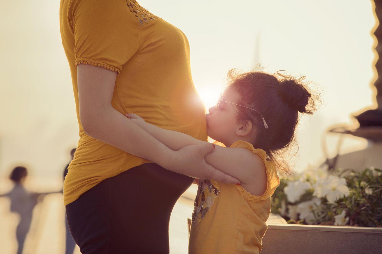 12 Überraschungen, mit denen Eltern beim zweiten Kind nicht rechnen: Kleinkind küsst Bauch der schwangeren Mutter.