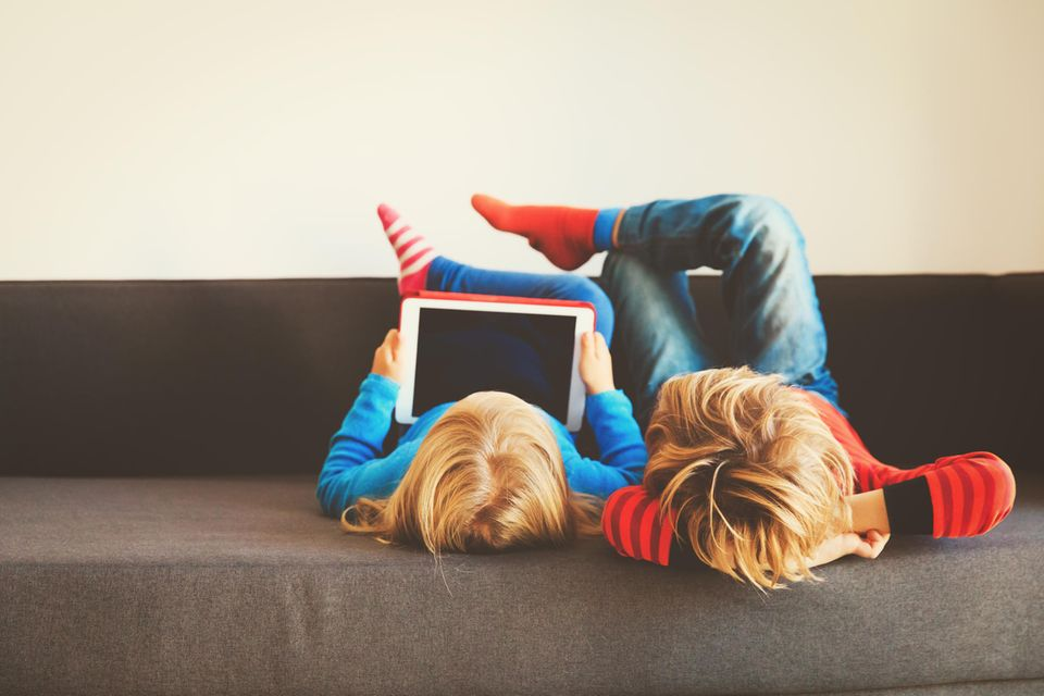 Kinder-Tablet im Test: Zwei Kinder auf dem Sofa schauen gemeinsam aufs Tablet.