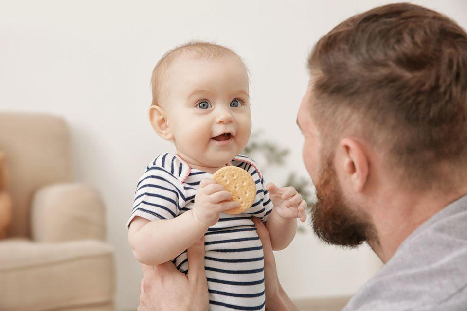 Baby mit Keks in der Hand