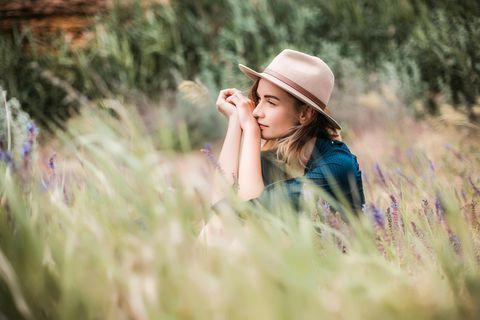 Wer diese Probleme hat, ist wahrscheinlich einfach zu nett: Frau sitzt im Gras und schaut in die Ferne.