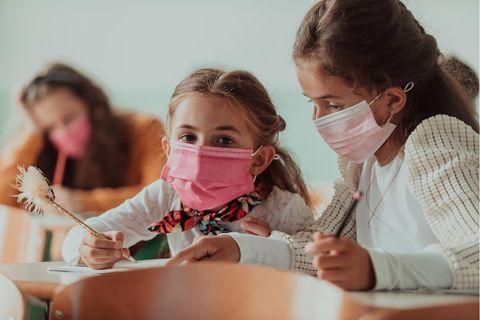 Zwei Mädchen mit Maskein der Schule.