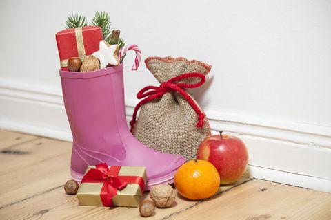 Nikolausgeschenke für Kinder: Pinker Gummistiefel mit Geschenk und Süßem gefüllt