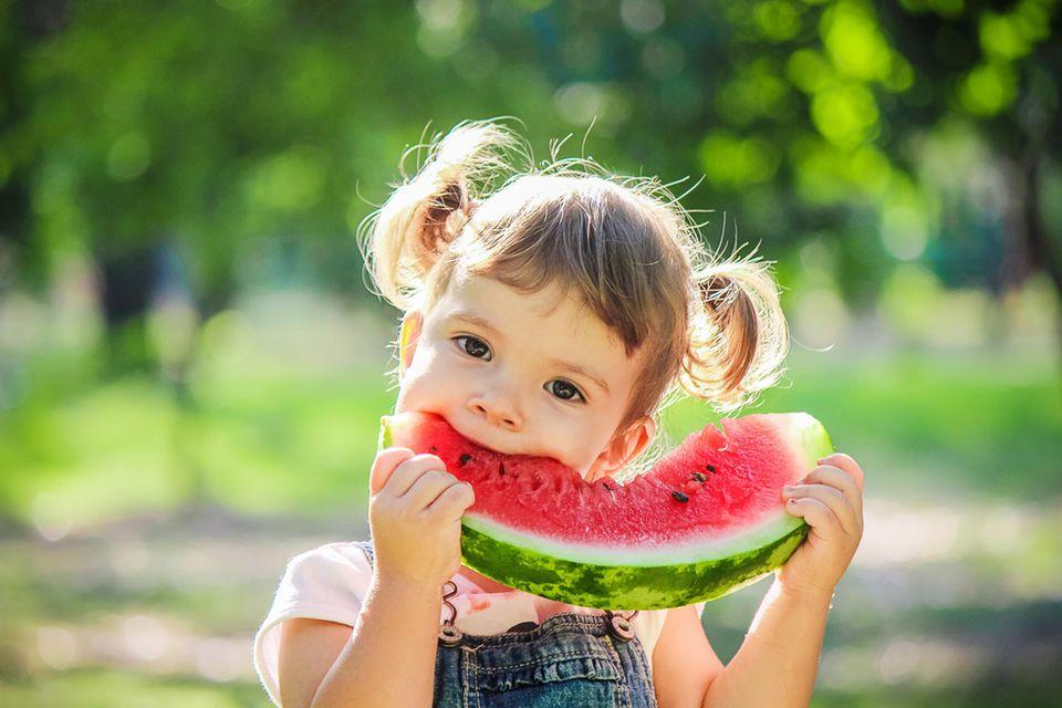 Zuckerarmes Obst: Kleines Mächen isst Wassermelone.