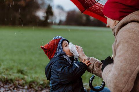 Richtige Kleiderwahl bei Kindern: Mutter putzt Kind die Nase bei Regen