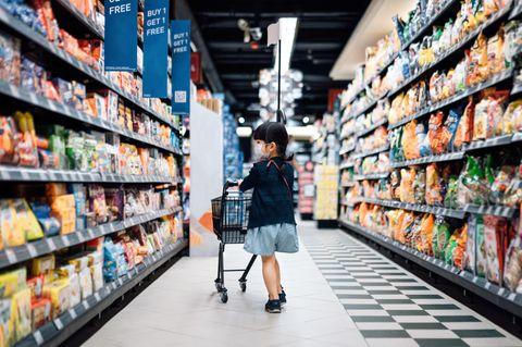 Ein Kind sitzt im Einkaufswagen seiner Mutter und nimmt etwas aus dem Kühlregal