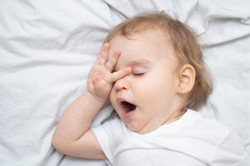 Gähnendes Kleinkind reibt sich die geschlossenen Augen