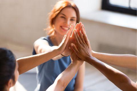 Frau gibt vier anderen Frauen ein high five